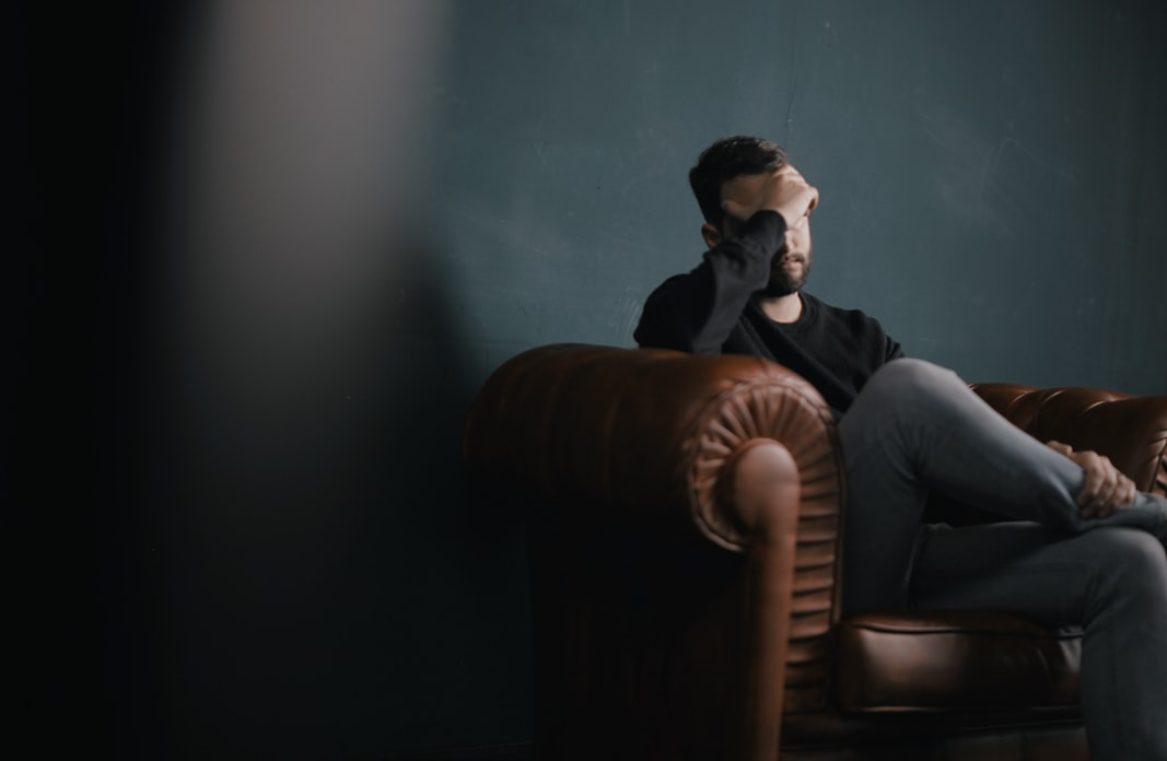 Man sitting in the dark, holding a hand on his face. Mental health struggling.