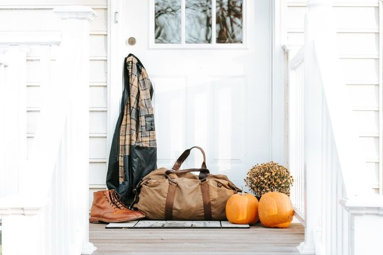 white doorway with coat, boots, holdall, pumpkins, and flowers on the porch in Manchester