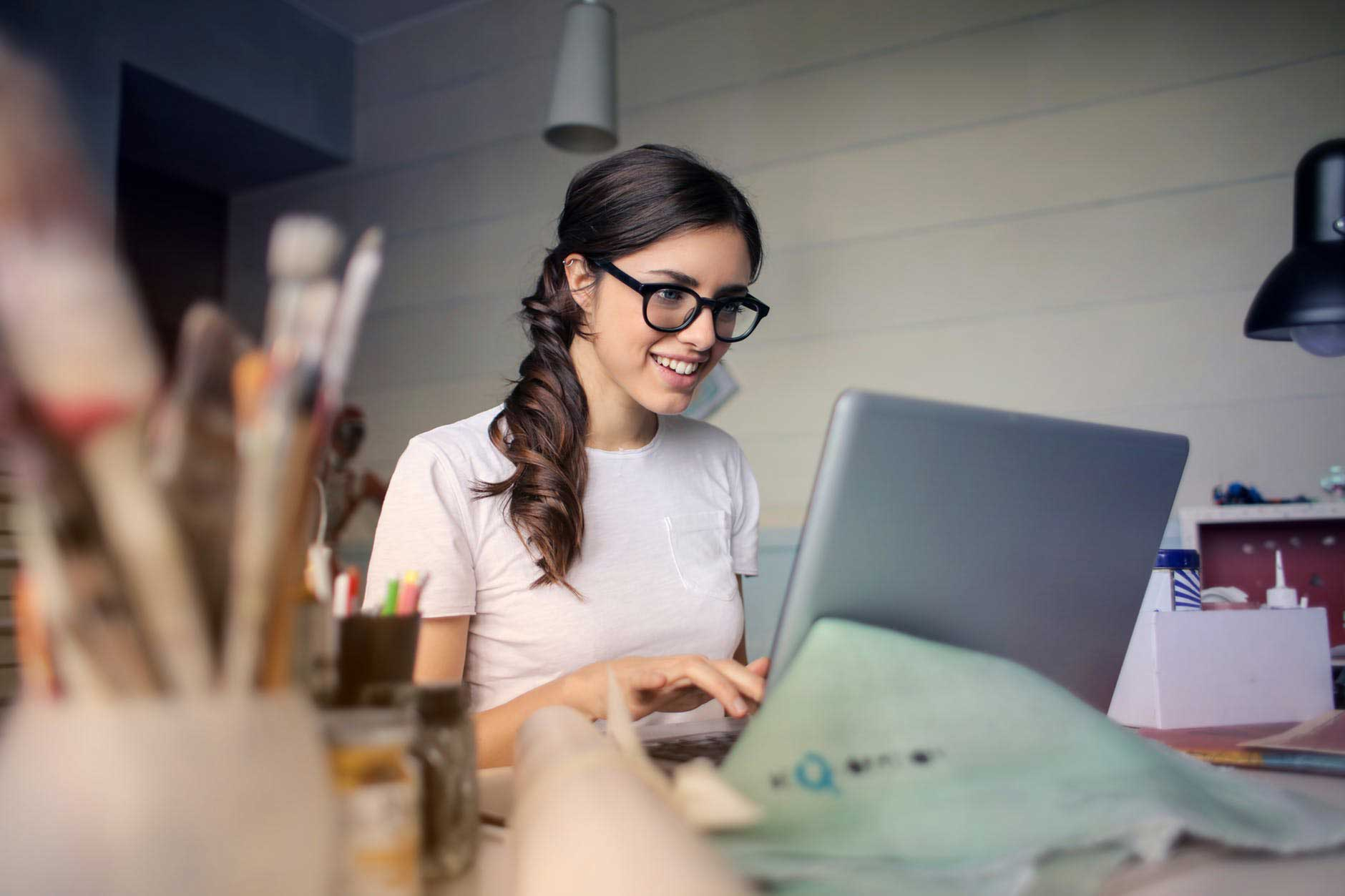 Woman working on laptop looking happy becuase of positive work-life balance in Leicester